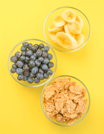 thinness: zenithal making bowls with cereal, bananas and blueberries, on yellow