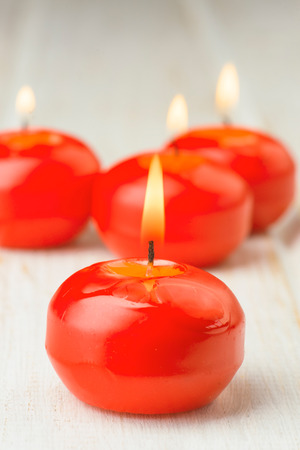 lighted: red lighted candles on white wood Stock Photo