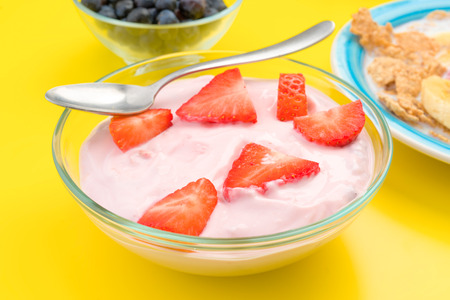 thinness: bowl of strawberry yogurt with sliced strawberries, on yellow background