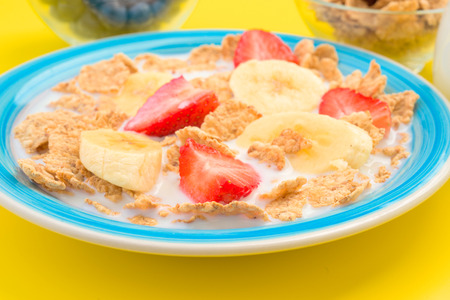 thinness: bowl of cereal with milk and bananas strawberries, yellow background