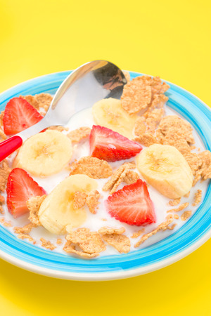 thinness: bowl of cereal with milk and sliced banana strawberry on white background
