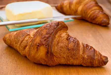 buttery: French croissant with butter baked on wood Stock Photo
