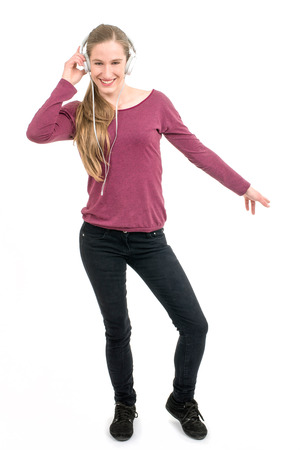 spontaneous expression: young girl with headphones dancing; on continuous white background Stock Photo