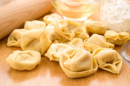 tortellini: tortellini uncooked on wooden board Stock Photo