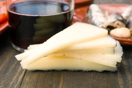 portions: sheep cheese in portions and glass of wine on rustic wood