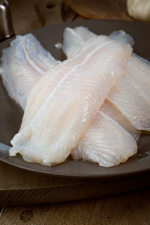 animalitos tiernos: filetes de pescado recién capturado en bruto en un plato sobre la madera