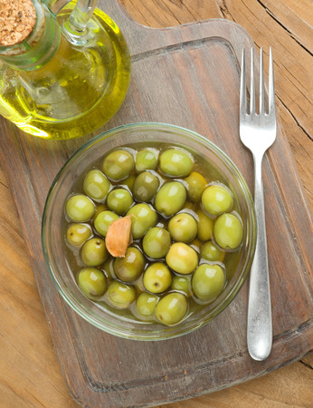 macerated: Vertical making bowl of olives and oil on old wood