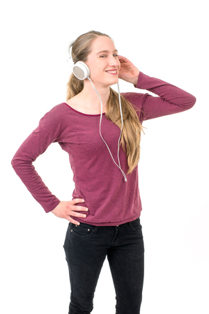 young girl with headphones dancing; on continuous white background Stock Photo