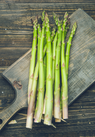 bunch of asparagus, on lackluster wooden board Stock Photo