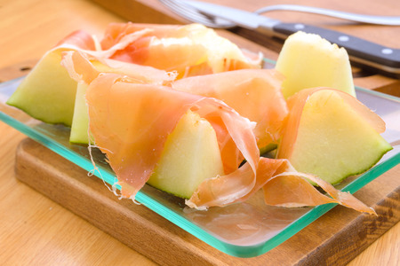 cut glass: melon with ham cut glass tray on wood