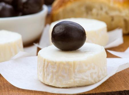 animalitos tiernos: queso de cabra con las aceitunas negras en la madera cl�sica Foto de archivo