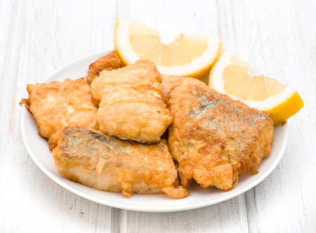 hake: pieces of fried hake dish with lemon on wooden Stock Photo