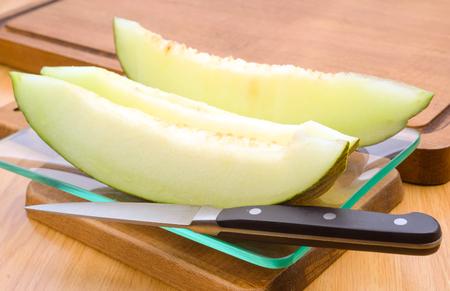 wood cut: melon cut glass tray on wood Stock Photo