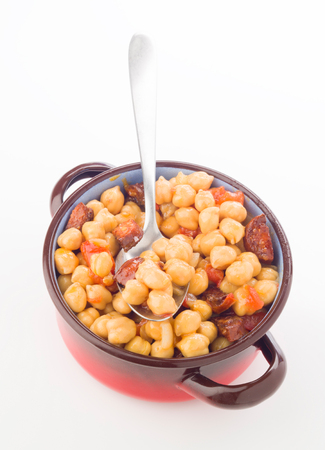 sausage pot: aereal view metal pot with chickpea stew with sausage on white