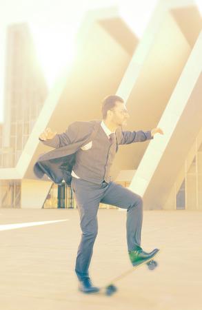 elegantly: elegantly dressed man flying with skateboard at sunset