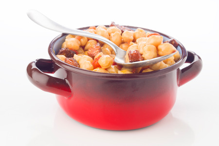 sausage pot: metal pot with chickpea stew with sausage, on white Stock Photo