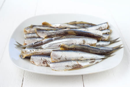sardinas: sardinas crudas en plato blanco sobre madera