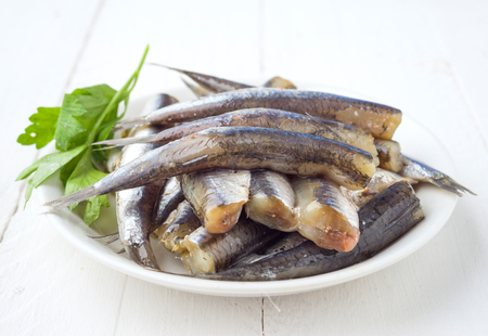 sardinas: bunch of raw sardines on plate with parsley on wooden