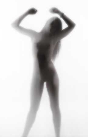 nudism: Diffuse silhouette of a woman silhouetting hands behind a curtain