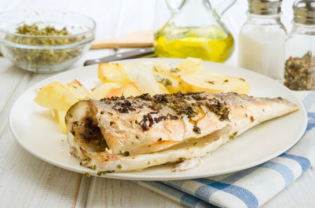 baked sea bass with potatoes in tray on wood