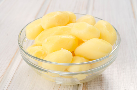 slotted: bowl of boiled potatoes on white wooden ruched