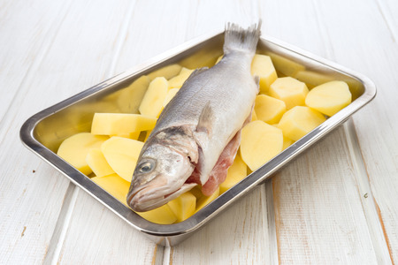 sheet steel: sea bass fish on potato wheels on cookie sheet steel on wood