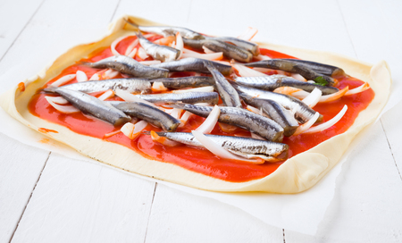 sardinas: preparation of sardines on puff pastry ready to bake on white wooden