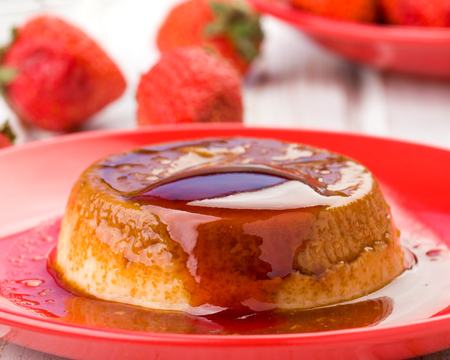 Homemade flan with strawberries, on red stage