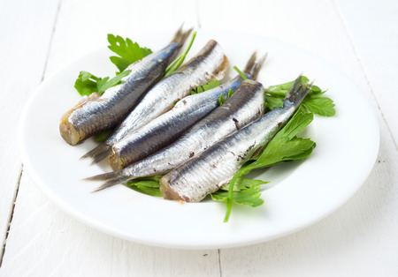 bunch of ordered raw sardines on plate with parsley on wooden Stock Photo