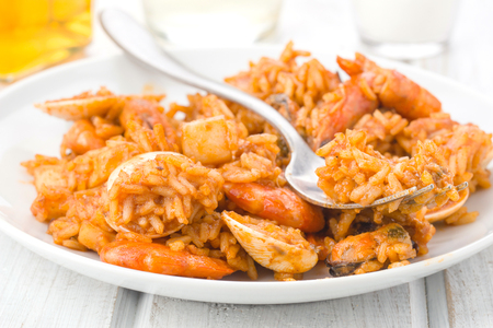 making close to rice dish with seafood on white wooden