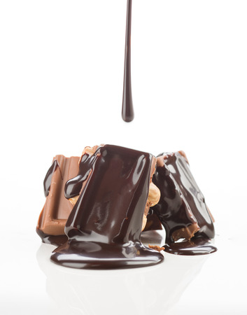 cataracts: liquid chocolate, falling into pieces of chocolate on white background