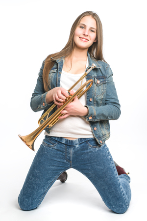 cornet: young woman kneeling with her trumpet on white background