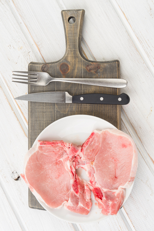 overhead shot two raw pork chops in  plate on white wood