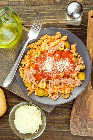 macaroni casserole with tuna olives and tomato sauce in rustic wooden Stock Photo