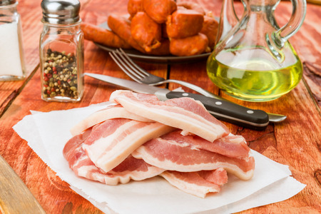 pieces of raw pork bacon on rustic wooden board