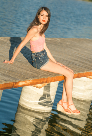 Young girl sitting on the dock of the lake at sunset