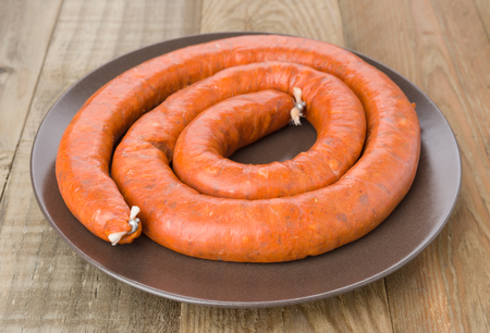 Uncooked sausage on brown porcelain dish on natural wood