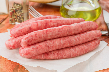 healt: raw white sausages on rustic wooden board