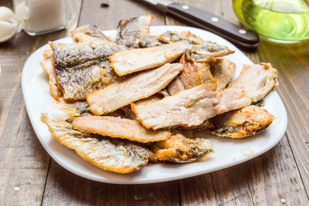 sardine fillets fried in white dish on wood