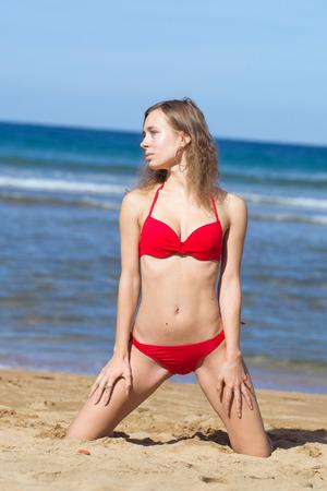 poses de modelos: modelo posa de rodillas en la arena en la playa al sol