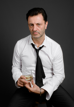 drunkenness: Sad mature man drinking alcohol, in studio