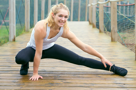 Girl athlete stretching practiced in the rain, outdoor