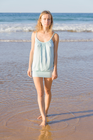 medium body: attractive young woman poses for the camera at the sea shore