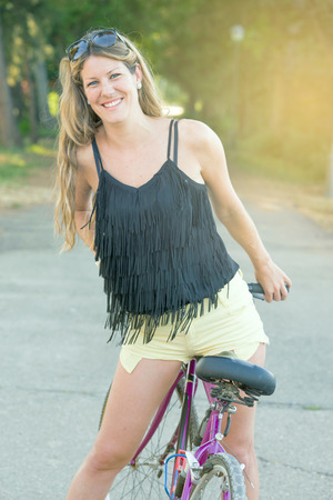 road bike: young woman leaning on her bicycle rests outdoors