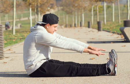 young man relaxing sport in a public park in a city in autumn at the sun