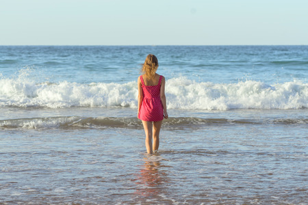 Young girl immersed in sea water dressed and barefoot
