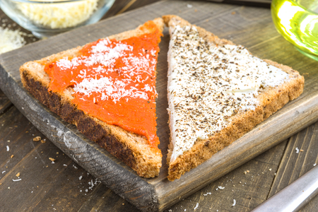 anointed: triangles of wholemeal bread spread with cream cheese and spicy sausage on wood Stock Photo
