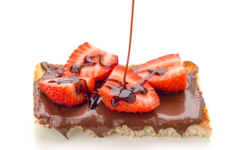 hilo de chocolate cayendo en chocolate tostado con mantequilla con fresas en rodajas, aislado en blanco Foto de archivo