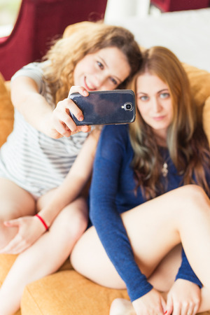 Young two friends using mobile phone on the couch at home
