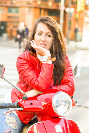Young girl with red jacket riding on her red motorbike Stock Photo
